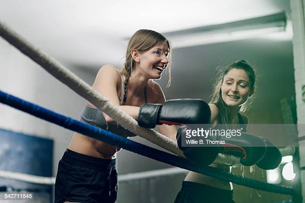 Two female fighters leaning on ropes