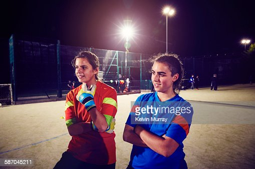 Two female football players under floodlights