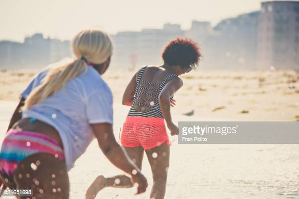 Two female friends acting playful at the beach.