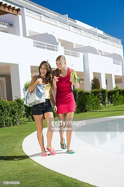 Two female friends by poolside on vacation