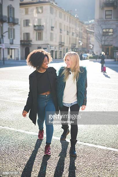 Two female friends chatting and strolling in town square