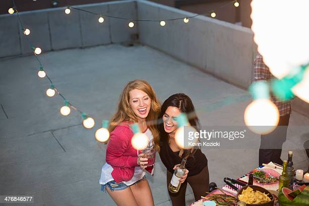 Two female friends dancing at rooftop party