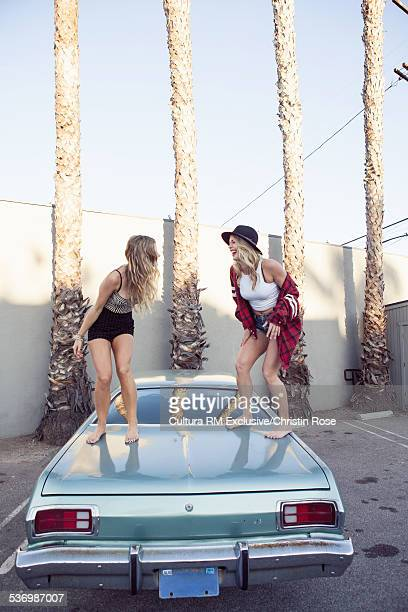 Two female friends dancing on car boot