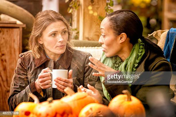 Two female friends discussing over a cup of coffee