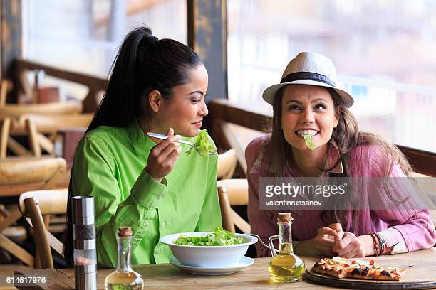 Two female friends eating and having fun in restaurant