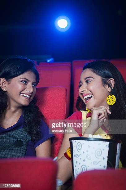 Two female friends enjoying movie with popcorns in a cinema hall