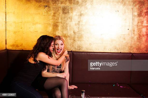 Two female friends having a laugh in nightclub