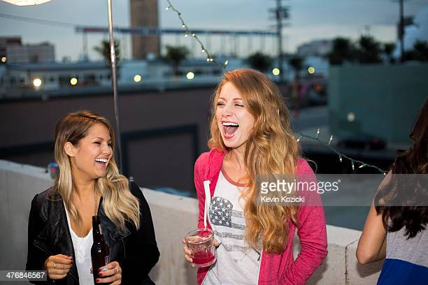 Two female friends having fun at rooftop party