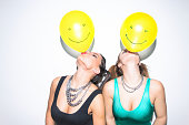 Two female friends having fun blowing up balloons on party