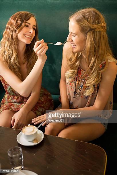 Two female friends having fun in a coffee shop