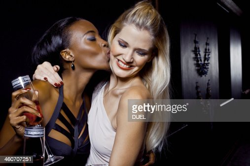 Two female friends hugging and kissing in nightclub