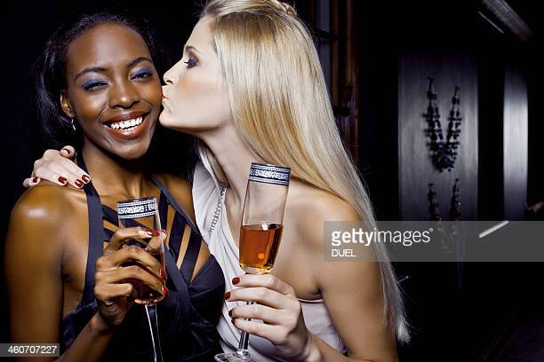 Two female friends hugging in nightclub