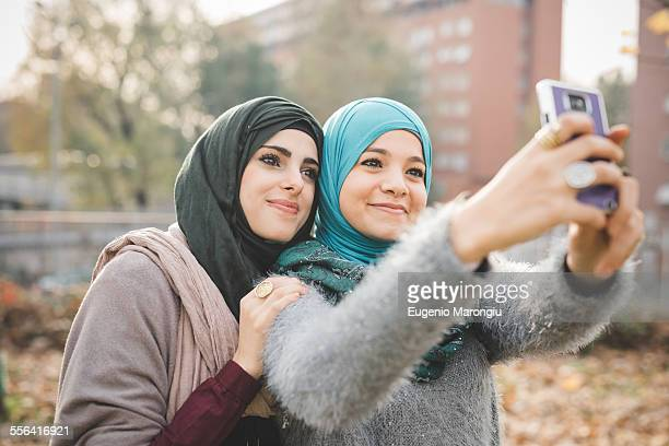 Two female friends in park posing for smartphone selfie