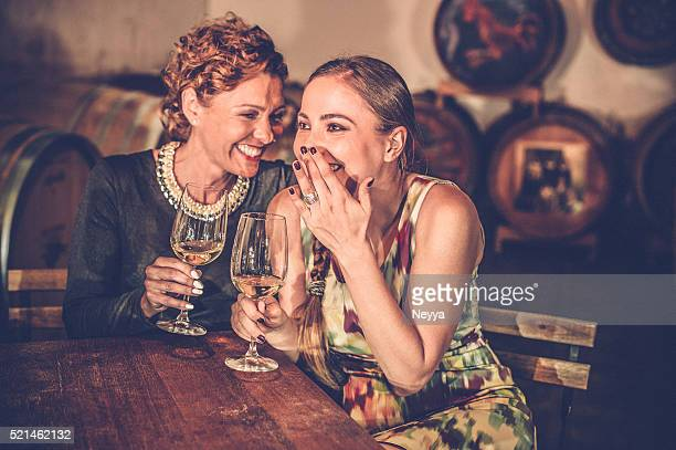 Two Female Friends in Wine Cellar Holding Wineglasses