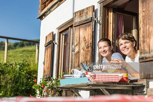 Two female friends looking out of chalet window, Tyrol, Austria
