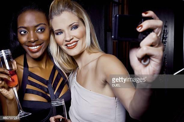 Two female friends making self portrait in nightclub