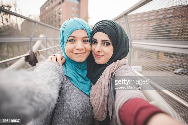 Two female friends on footbridge taking selfie