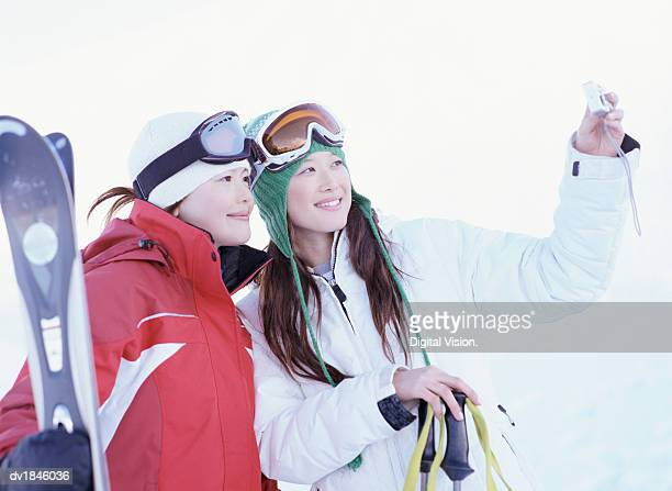Two Female Friends Photographing Themselves on a Skiing Holiday
