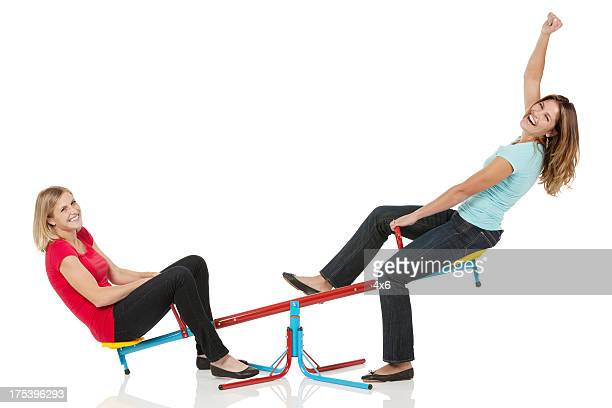 Two female friends playing on a seesaw