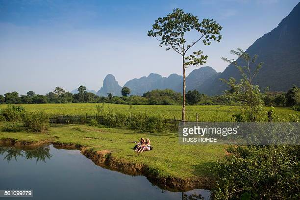 Two female friends relaxing on Nam Song riverbank, Vang Vieng, Laos