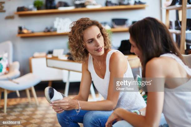 Two female friends sitting and talking in a boutique