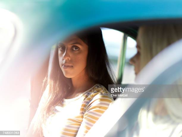 Two female friends sitting in car, pensive expressions