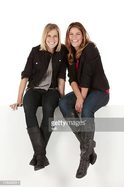 Due amiche seduto su un ripiano