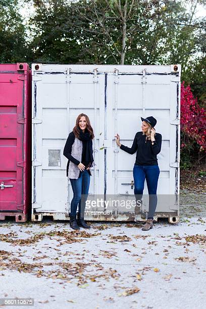 Two female friends standing in front of a container