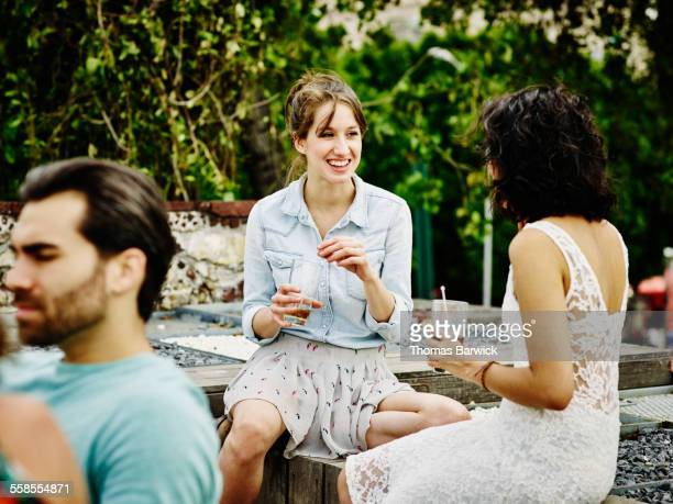 Two female friends talking over drinks