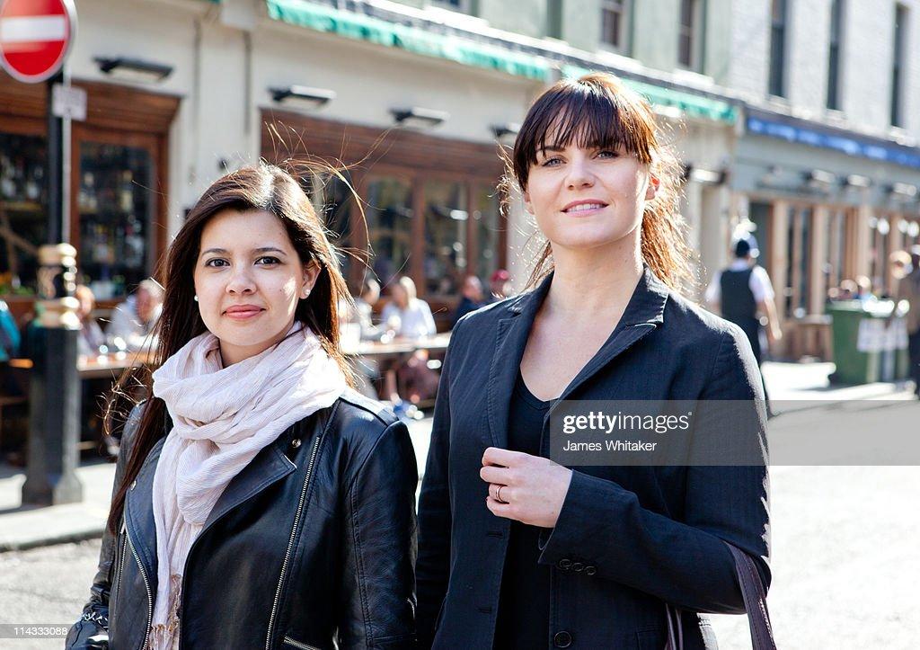 Two female friends walking down the street : Stock Photo