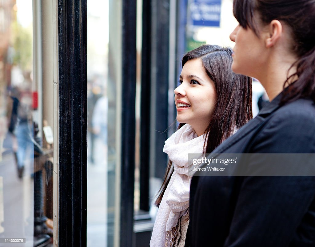 Two female friends window shopping : Stock Photo