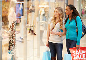 Two Female Friends Window Shopping With Bags Smiling