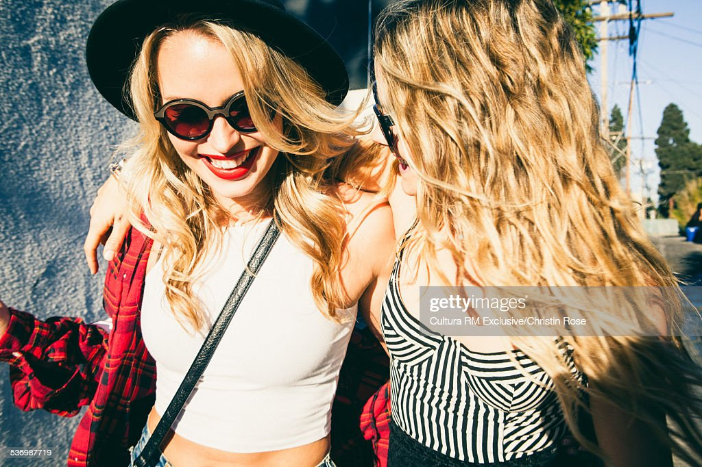 Two female friends with arms around each other : Stock Photo