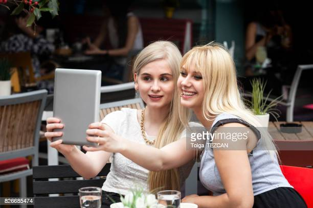 Two Female Frineds Holding Tablet and Laughing in Coffee