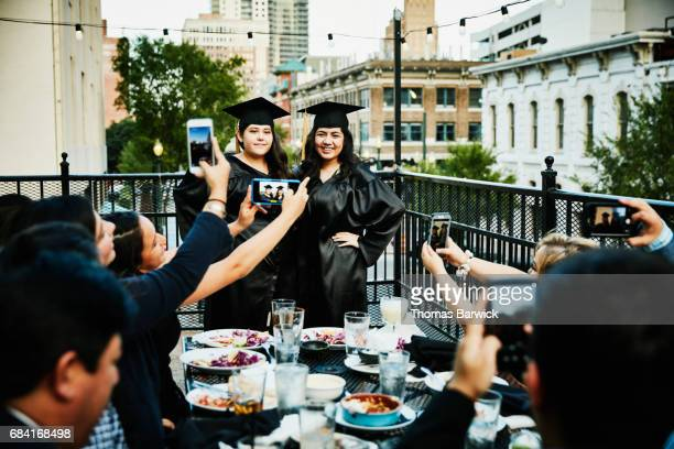 Two female graduates posing for pictures for family during meal on restaurant deck
