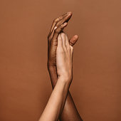 Close up of two female hands together on brown background. Hands of african and caucasian female.