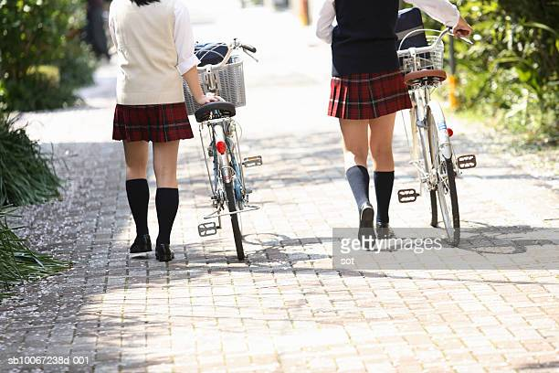 Two female high school students (17-18) walking with bicycles, rear view, low section