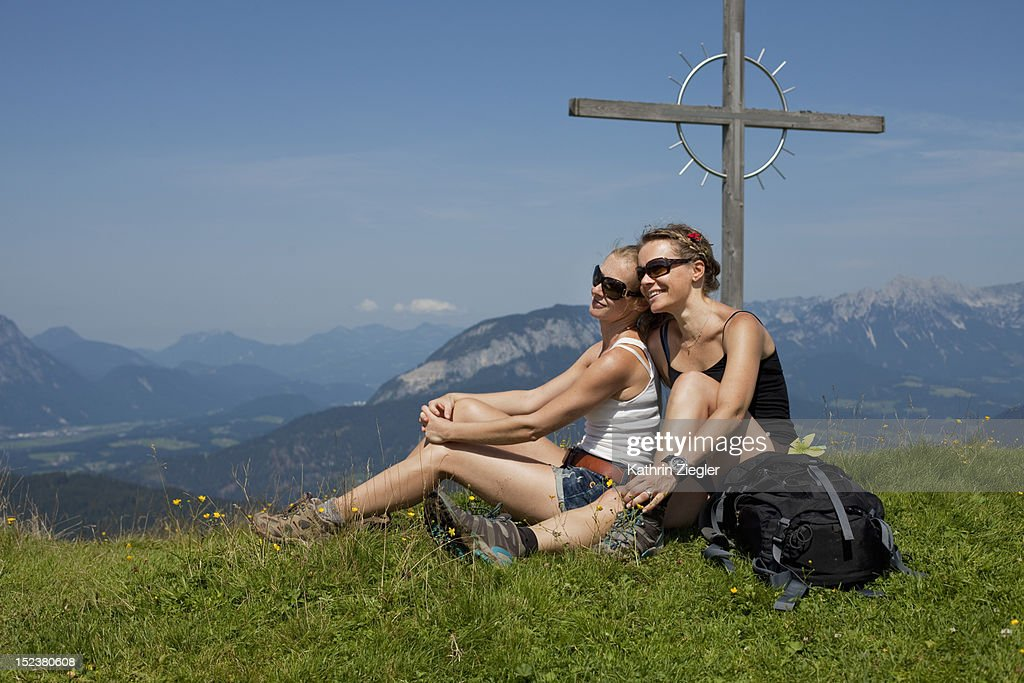 two female hikers at summit cross : Stock Photo