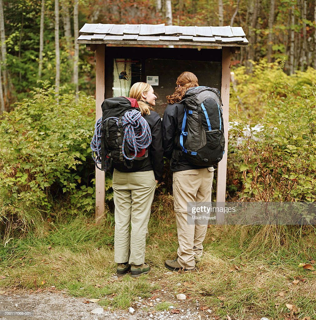 Two female hikers, standing by information booth at trail head : Stock Photo