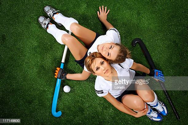 two female hockey players sitting at sport field