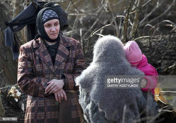 Two female members of a Russian doomsday cult with a baby converse near their compound in Nikolskoye on April 3 2008 Russian authorities played a...