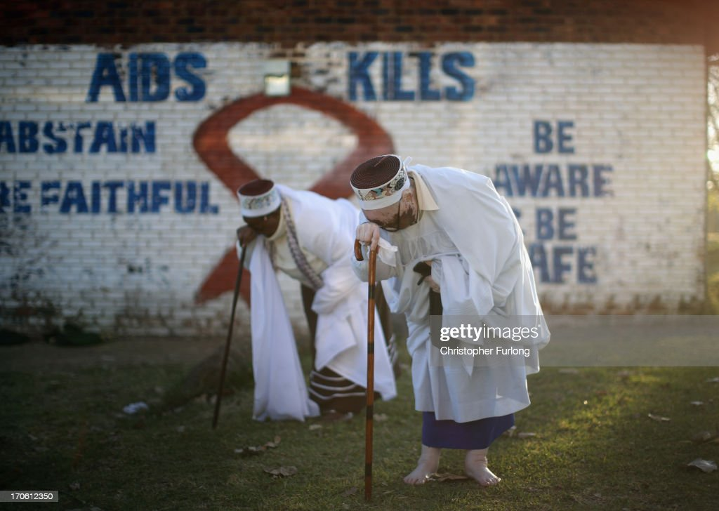 Two female members of the Church of Nazareth pray as they take part in a service at Rockville School, in Soweto on June 15, 2013 in Johannesburg, South Africa. The Baptist church, which is a mixture of Zulu tradition and Christianity, continued their daily life as the former South African President and leader of the anti-apartheid movement who is spending a seventh night in hospital. It has been reported that he is responding better to treatment for a recurring lung infection.