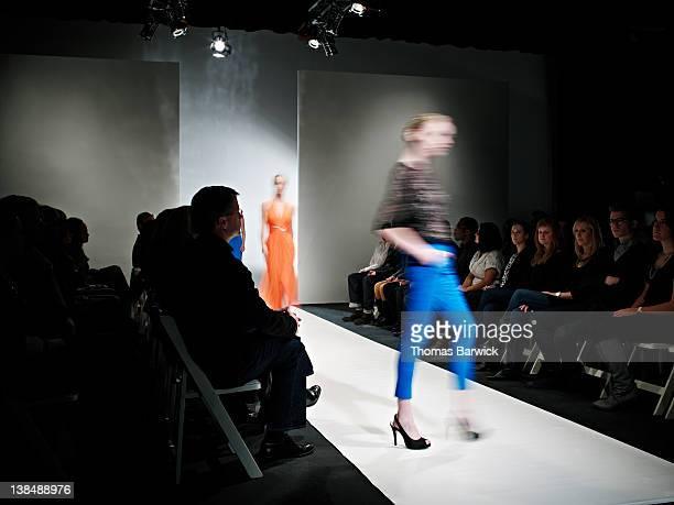 Two female models walking on catwalk motion blur