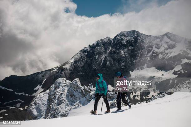 Two Female Mountaineers Crossing a Glacier with a huge Mountain Ridge Behind them.