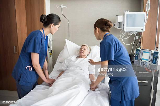 Two female nurses reassuring senior woman in hospital bed
