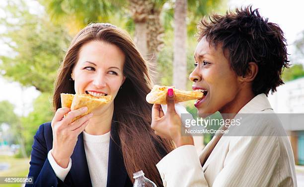Two female office workers colleagues gossiping outdoors while eating pizza