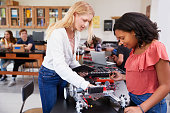 Two Female Pupils Building Robotic Vehicle In Science Lesson