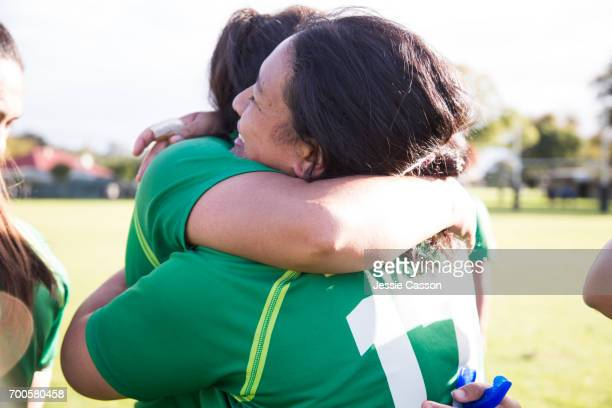 Two female rugby players embrace after match