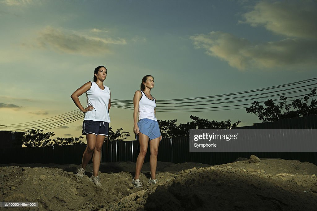 Two female runners standing on pile of dirt : Stock Photo