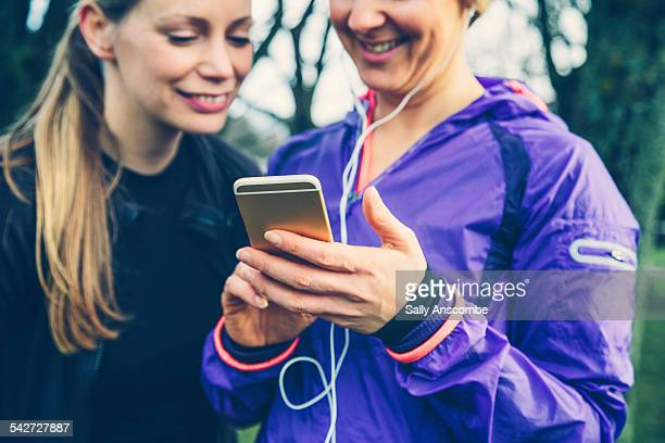 Two female runners using a smart phone